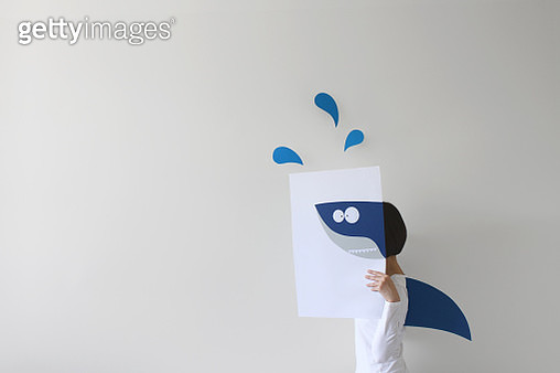 Woman holding paper with a shark drawing and wearing a shark fin - gettyimageskorea