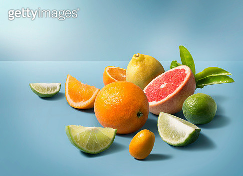 A group of mix citrus fruits on clean blue background. Studio shot image. - gettyimageskorea