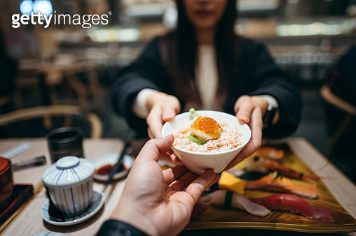 Young woman passing a bowl of seafood donburi across table to a friend during lunch in a Japanese restaurant - gettyimageskorea