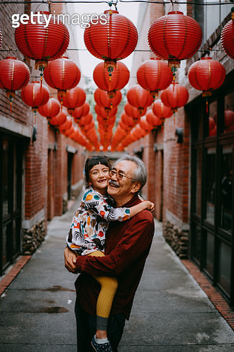 Japanese grandfather holding his Eurasian granddaughter and smiling on street with red lanterns, Taiwan - gettyimageskorea