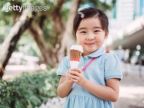 Lovely little girl having ice-cream joyfully - gettyimageskorea