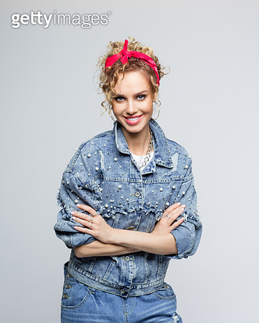 Portrait of blond curly hair confident young woman wearing white t-shirt, denim jacket and red bandana, standing with arms crossed and smiling at camera. Studio shot on grey background. - gettyimageskorea