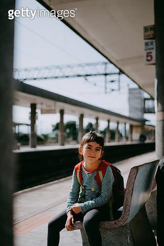 Beautiful preschool mixed race girl sitting on bench at railway station platform, Taiwan - gettyimageskorea