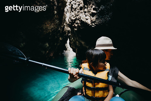 Mother and child exploring a sea cave by kayak - gettyimageskorea