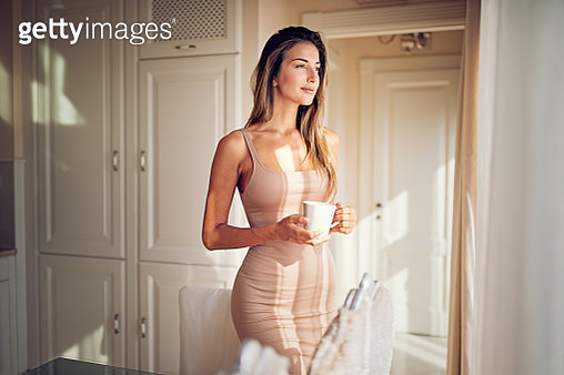 Young ,beautiful woman is looking through the window and drinking coffee in the morning - gettyimageskorea