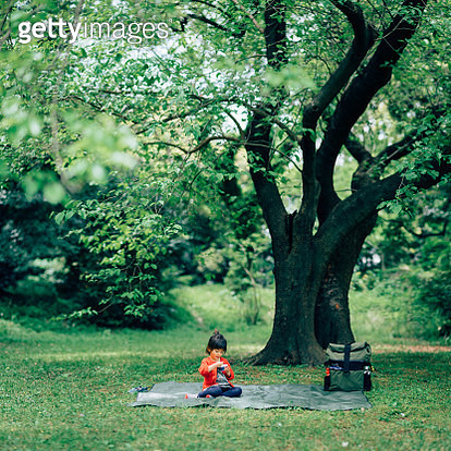 Little girl sitting and eating alone under tree in park - gettyimageskorea