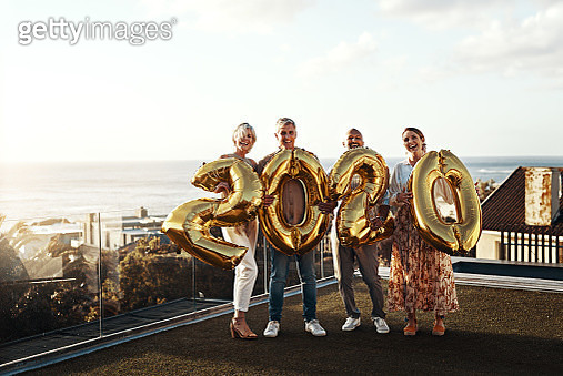 """Full length portrait of an affectionate family holding up balloon numbers reading """"2020"""" while celebrating a new year outdoors - gettyimageskorea"""