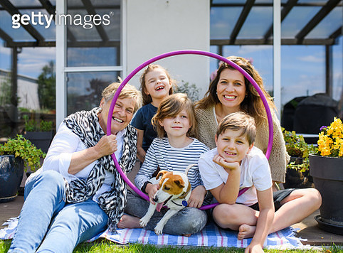 Portrait of family with children and grandmother sitting in backyard outdoors. - gettyimageskorea