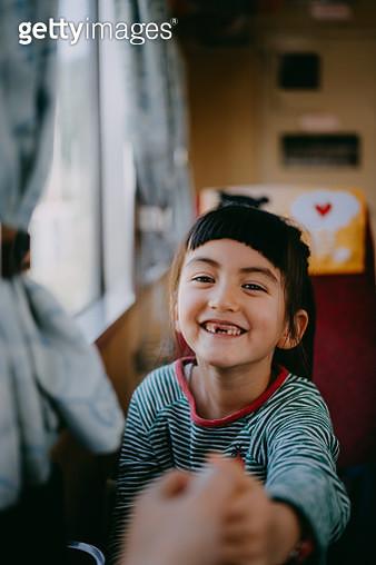 Portrait of cute little Eurasian girl in train - gettyimageskorea