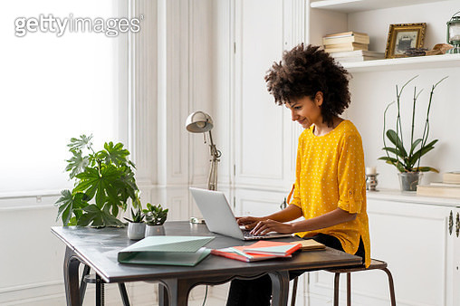 Woman sitting at desk, working, using laptop - gettyimageskorea