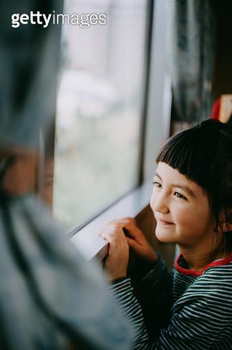 Adorable little Eurasian girl looking outside train window - gettyimageskorea
