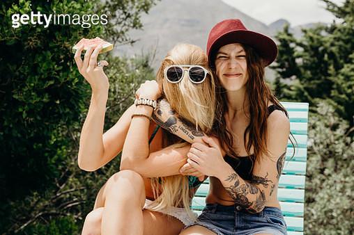 Happy oddball girlfriends embrace outdoors with watermelon in hand - gettyimageskorea