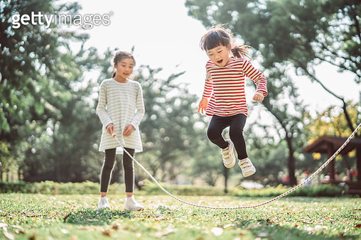 Young family jumping rope joyfully on the lawn - gettyimageskorea