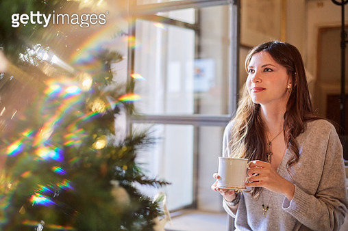Christmas lifestyle themes. People celebrating Christmas at home. Shot in Barcelona with Spanish models. Young woman dreamingly looking at the Christmas tree. - gettyimageskorea