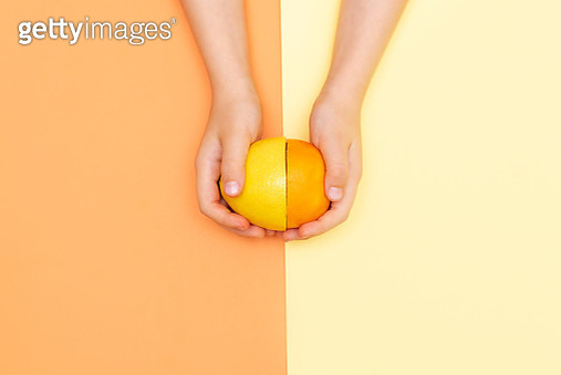 Hand holds lemon slice. - gettyimageskorea
