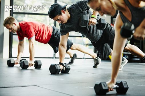 Group of friends doing pushups with dumbbells in gym gym - gettyimageskorea