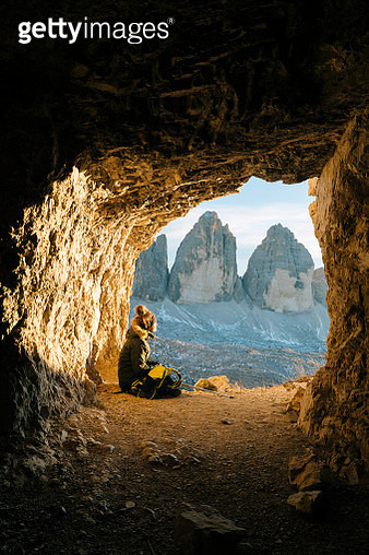 Female hiker takes a break in mountain cave, enjoys view - gettyimageskorea