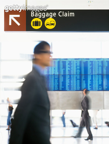 Businessmen walking in front of flight schedule board, blurred motion - gettyimageskorea