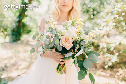 Midsection Of Bride Holding Flower Bouquet While Standing At Park - gettyimageskorea