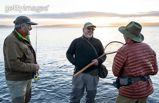 Two fly fisherman talk with their guide about new techniques while fly fishing for searun coastal cutthroat trout at a beach on the north west coastline of the USA. - gettyimageskorea