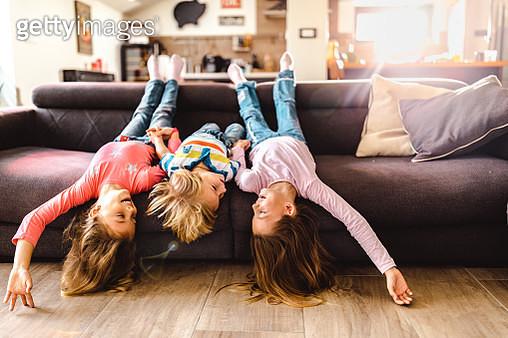 Playful kids having fun on sofa in the living room. - gettyimageskorea