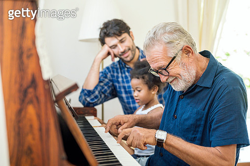Family spend time happy together. Grandfather playing piano with his granddaughter and son together in living room at home. - gettyimageskorea