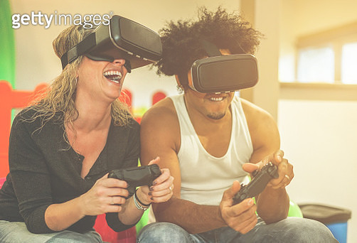 Happy Couple Wearing Virtual Reality Simulator While Playing Video Game At Home - gettyimageskorea