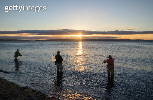 Two fly fishermen cast for searun coastal cutthroat trout and salmon at sunrise with their guide standing between them at the salt water beach at a beach on the north west coastline of the USA. - gettyimageskorea