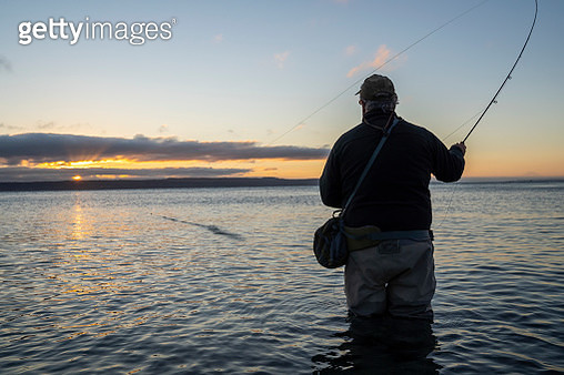 A silhouette view of a fly fisherman casting for salmon and searun coastal cutthroat trout from a salt water beach at a beach on the north west coastline of the USA. - gettyimageskorea