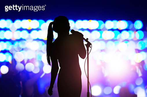 Silhouette of woman with microphone singing on concert stage in front of crowd - gettyimageskorea