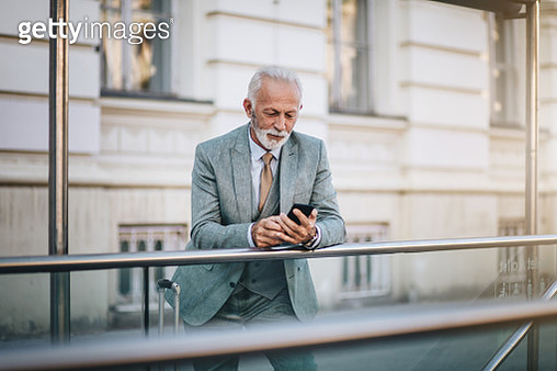 Bearded businessman texting on a mobile phone - gettyimageskorea