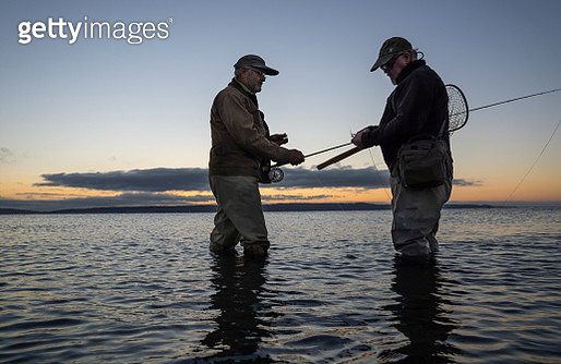 A male fly fisherman watches his guide work putting on a new fly to try for salmon or trout on  a salt water beach at Fort Flagler State Park in northwest Washington State, USA - gettyimageskorea