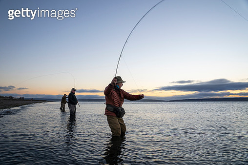 Two fly fishermen cast for searun coastal cutthroat trout and salmon with their guide standing between them on a salt water beach  on a beach on the west coast of the USA - gettyimageskorea
