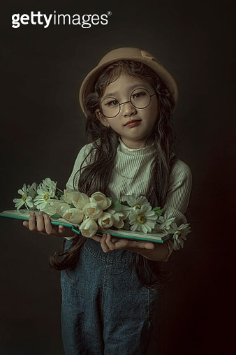 Portrait Of Girl Holding Book With Flowers Against Black Background - gettyimageskorea