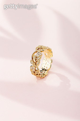 Floral design gold ring with diamonds on pink background with leaves shaped shadow - gettyimageskorea