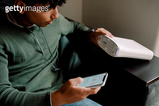 Teenage boy holding router while checking Wi-Fi connection on mobile phone at home - gettyimageskorea