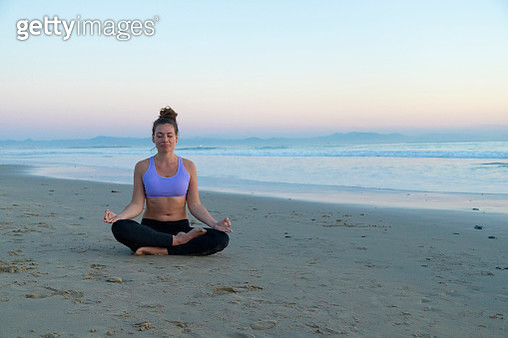 Woman meditating on the beach in the evening - gettyimageskorea