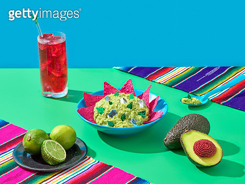 A bowl of guacamole with pink nachos a red drink, avocados and lemons. - gettyimageskorea