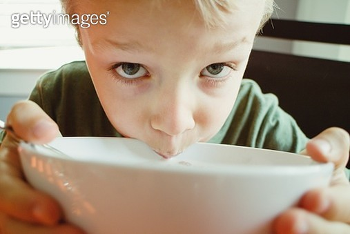 Close-Up Portrait Of Boy Drinking Cereal - gettyimageskorea