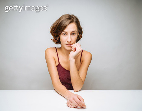 Cute young woman sitting at table - gettyimageskorea