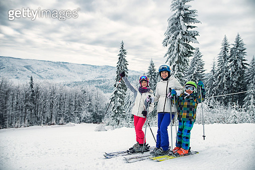 Mother and kids skiing together on winter day - gettyimageskorea