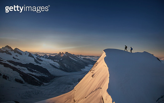 Climbers reaching the top of a mountain - gettyimageskorea