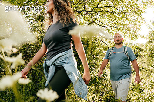 Caucasian couple walking in the park. Young woman and overweight man walking through the woods. - gettyimageskorea