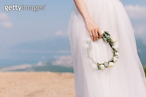 Midsection Of Bride Holding Wreath Against Sky - gettyimageskorea