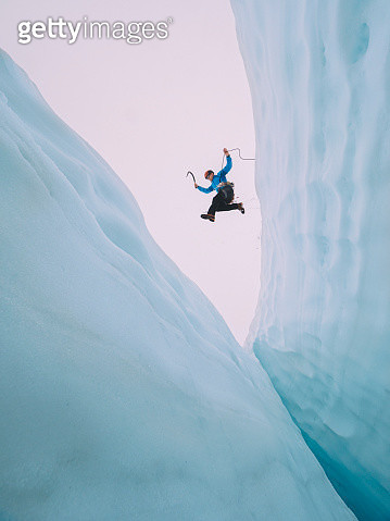 A mountain climber makes huge jump over a large and intimidating crevasse on The Serratus Glacier in British Columbias Coast Mountain Range. - gettyimageskorea
