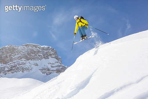 Young man back country skiing in deep snow, powder snow. - gettyimageskorea