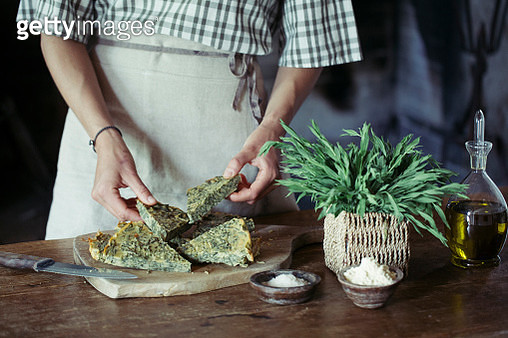 Young woman garnishing homemade chickpea and herb cake - gettyimageskorea