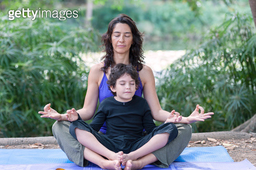 Hispanic mother and son practicing yoga - gettyimageskorea