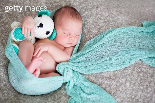 Sleeping newborn baby boy in bed, hugging little k - gettyimageskorea