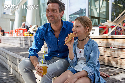 Father with drink and daughter with ice cream cone at an outdoor cafe - gettyimageskorea